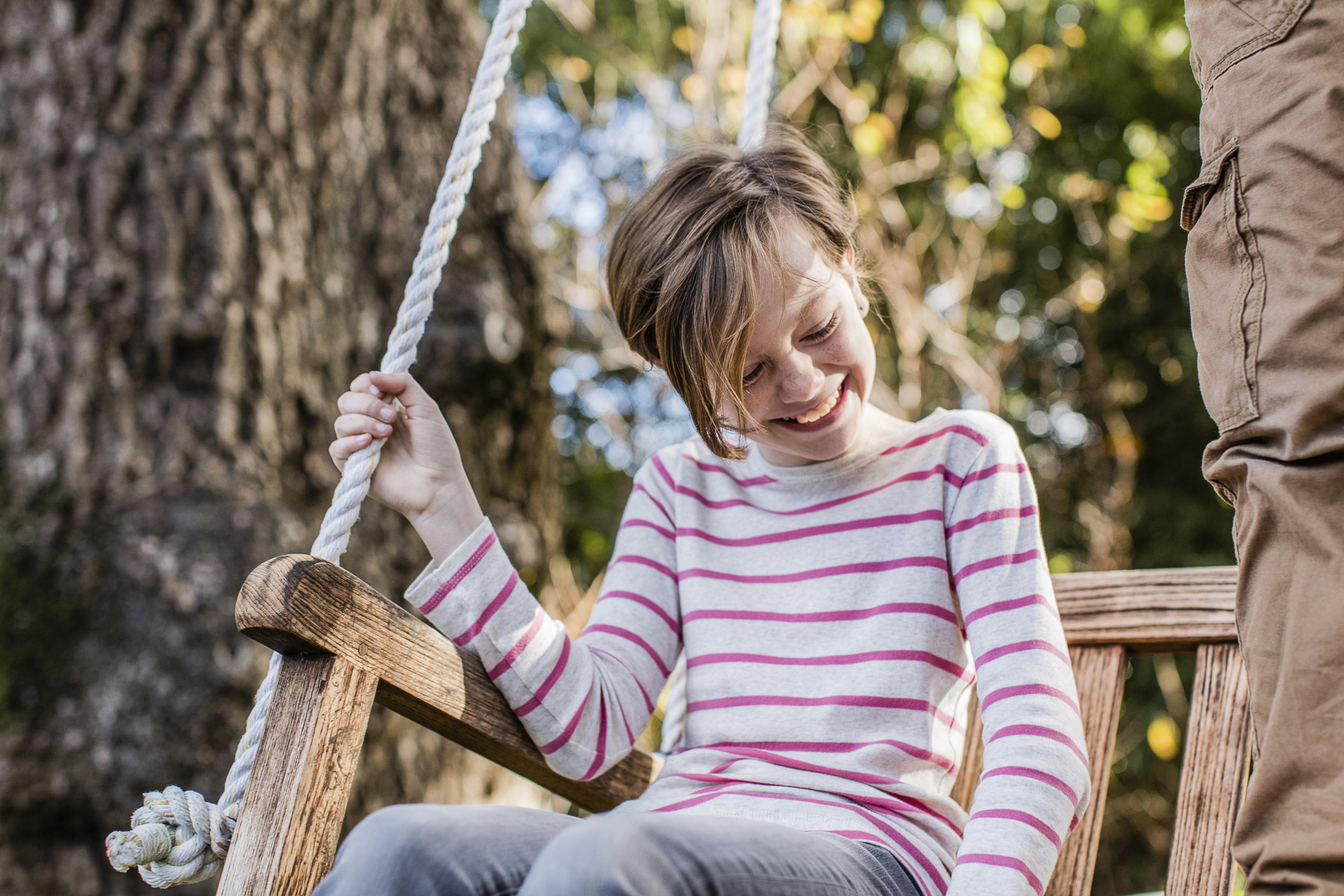 Young Girl on a Bench Swing in a Backyard