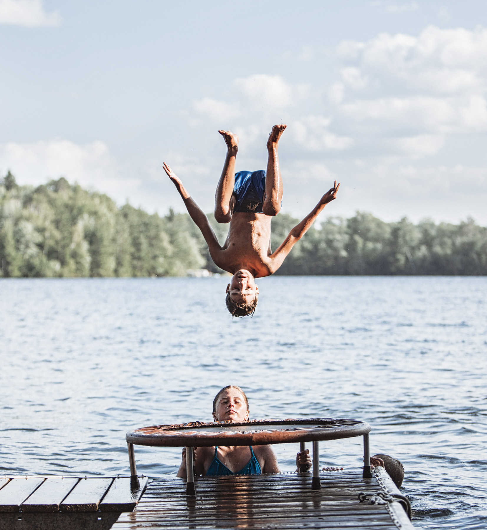Boy Jumping into Lake over Girl