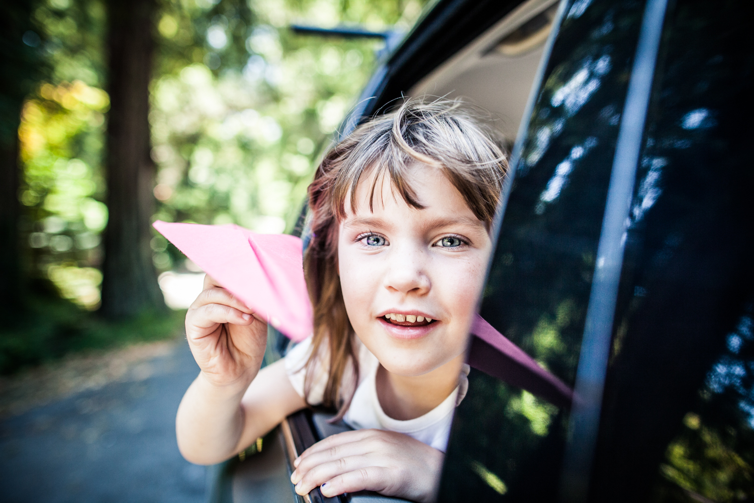 young Girl with a Paper Airplane Hanging out a Car Window