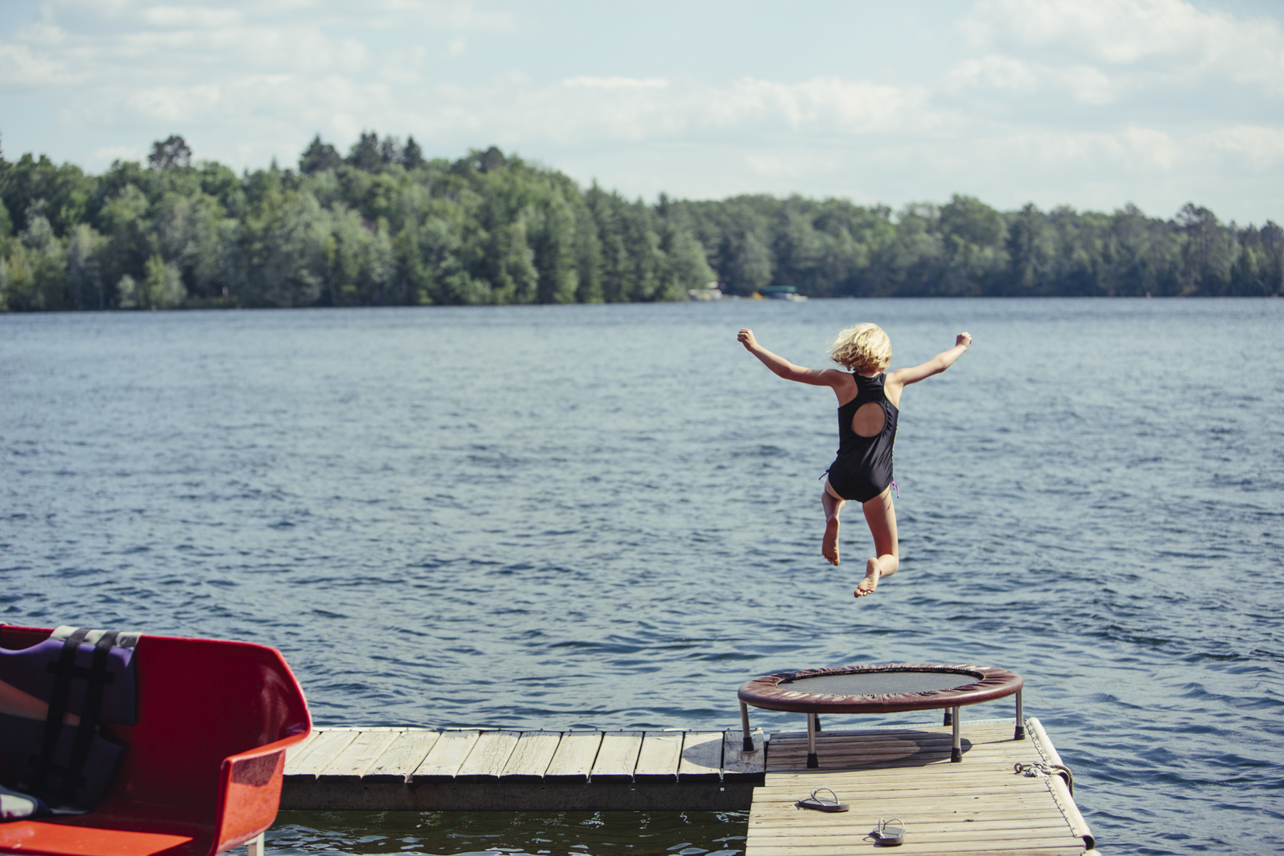 Young Girl Jumping into Lake
