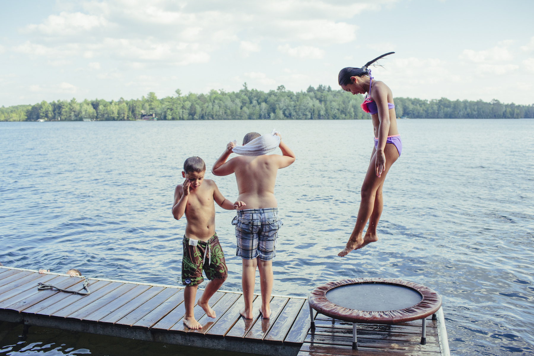 Girl Jumping on Trampoline into a Lake